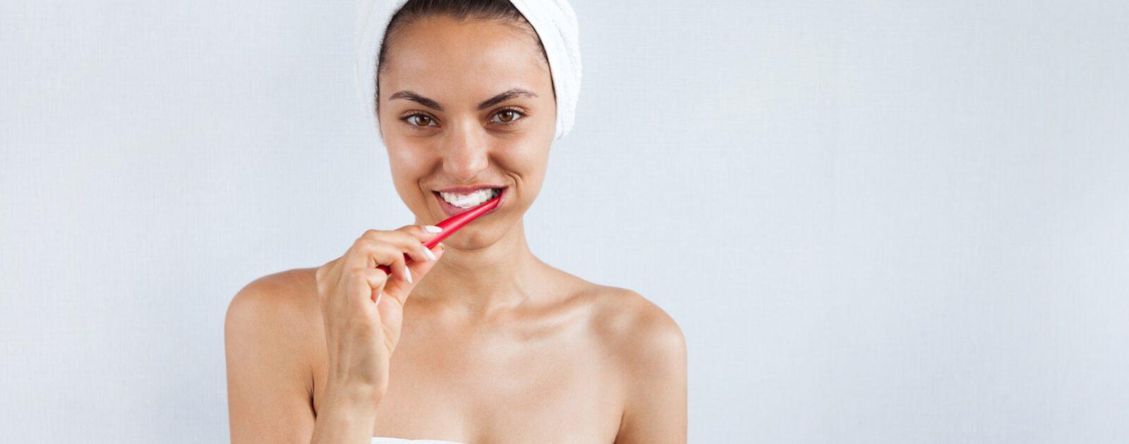 Eine Frau putzt sich mit einer Vitamin B12 angereicherten Zahnpasta die Zähne.
