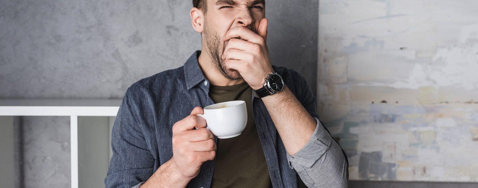Ein Mann ist in Folge eines Vitamin B12-Mangels müde und gähnt.