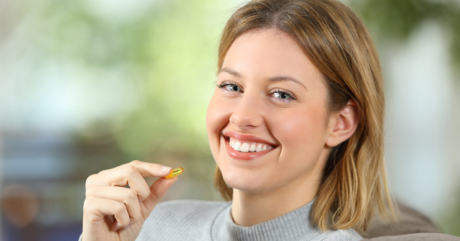 Veganerin nimmt Nahrungsergänzungsmittel ein, um ihren Vitamin B12-Bedarf zu decken.