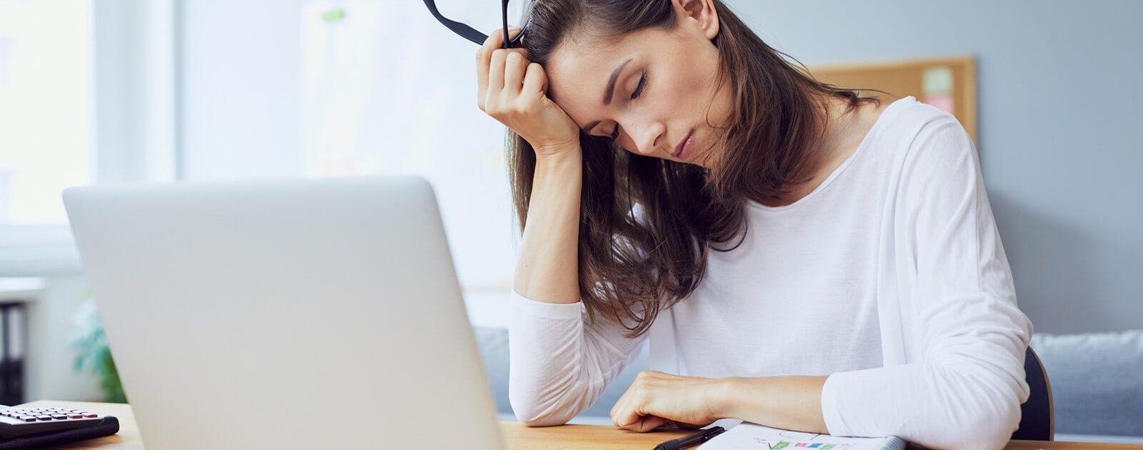 Eine Frau schläft aufgrund eines Vitamin B12-Mangels bei der Arbeit ein.